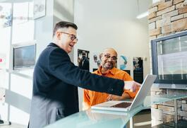 Men standing pointing at computer