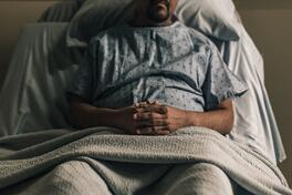 a-man-propped-up-in-hospital-bed-with-hands-crossed-scaled-e1615388751275
